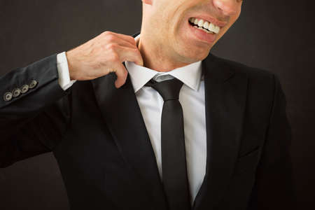 to tight: Business man pulling his shirt of his neck Stock Photo