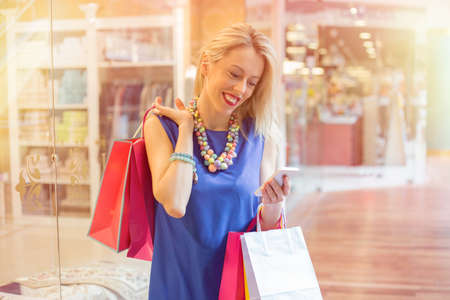 one person with others: Woman shopping and texting on smartphone