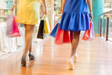 shopaholism: Two women walking with shopping bags at the shopping mall