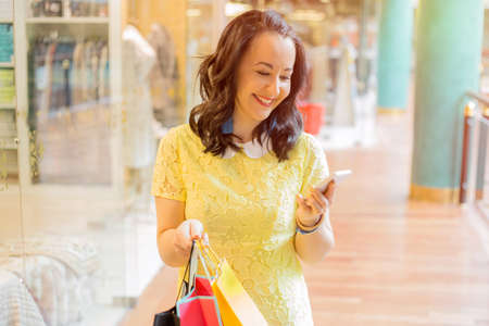 one person with others: Woman looking at smartphone while shopping