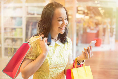 one person with others: Woman using smartphone while shopping Stock Photo