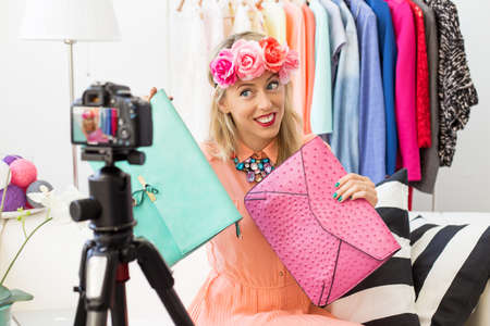 Fashion blogger taking picture and holding two clutch bags