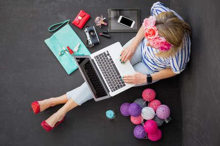 femme moderne assis sur le sol avec l'ordinateur sur ses genoux