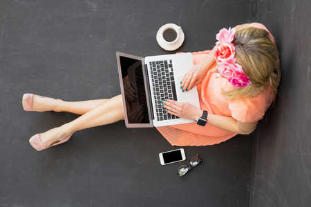 woman sitting with laptop: Beautiful woman sitting on the floor and using computer Stock Photo