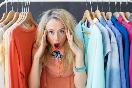 deciding: Stressed woman deciding what to wear Stock Photo