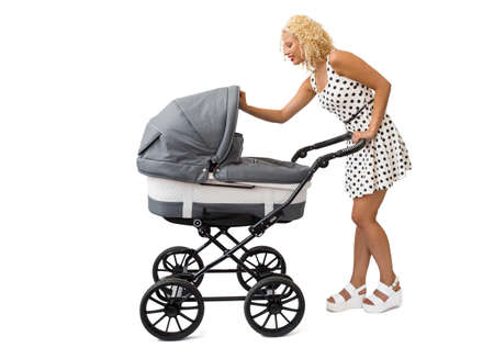 Mother looking into the baby carriage Stock Photo