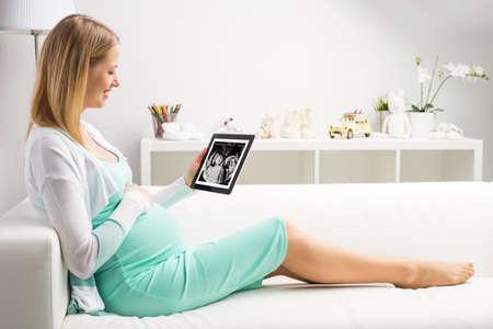 feto: Mujer embarazada que mira a sus bebés primeros resultados de la ecografía en la tablilla