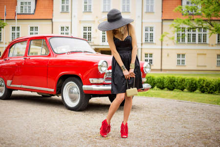 heals: Glamorous and sexy woman in high heals standing in front of retro car