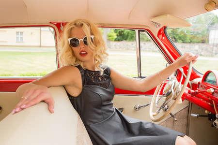 Uitstekende vrouw die een retro auto rijdt Stockfoto