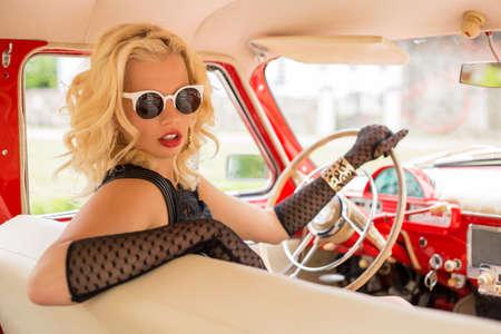 Sexy vrouw met zonnebril rijden een retro auto Stockfoto