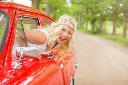 Happy and cheerful woman hanging out of vintage car