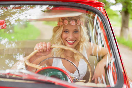 drivers seat: Woman sitting in drivers seat in retro car and smiling
