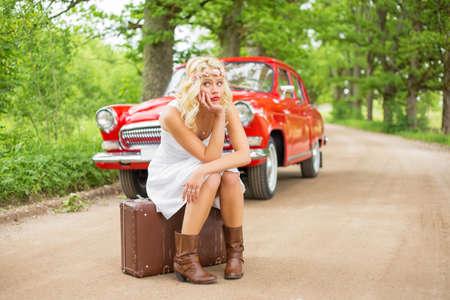 Triste donna seduta su valigetta e in attesa di aiuto Archivio Fotografico - 64292938