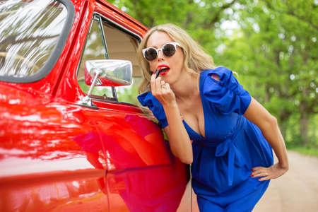 Glamorous womanlooking in auto zijspiegel en zetten lippenstift