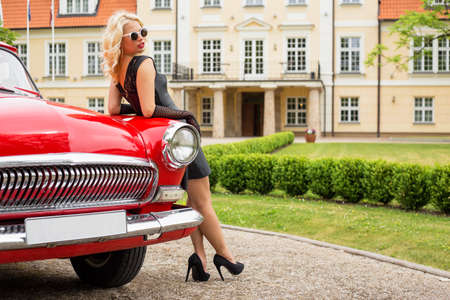 heals: Sexy woman leaning against red vintage car Stock Photo