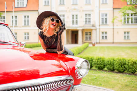 Flirty and glamorous woman with red retro car