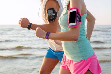Couple running on the beach with their mp3 players