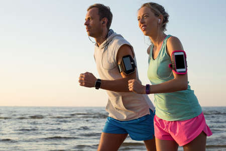 plugged in: Couple running on the beach during sunset with their headphones plugged in