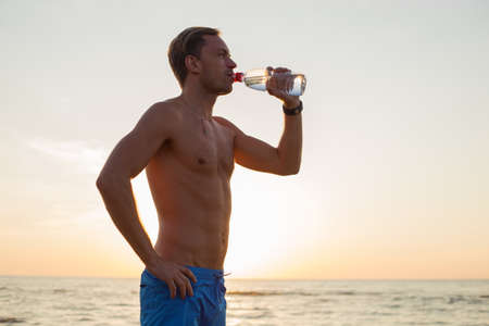 man drinking water: Fit man drinking water after workout