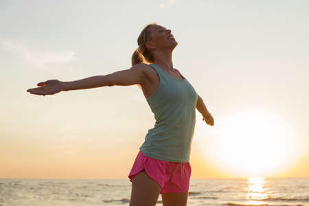 strecthing: Happy and fit woman meditating on the beach