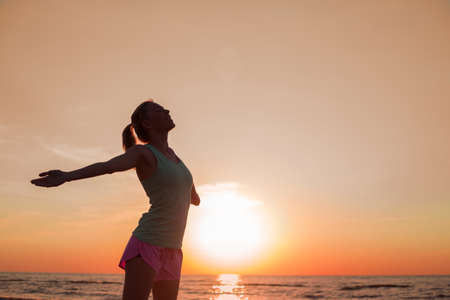 Gelukkig en gezond vrouw in zonsondergang Stockfoto