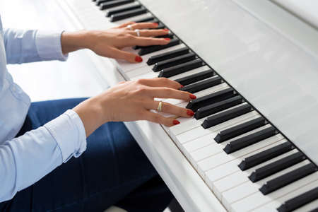 Woman playing white piano Stock Photo