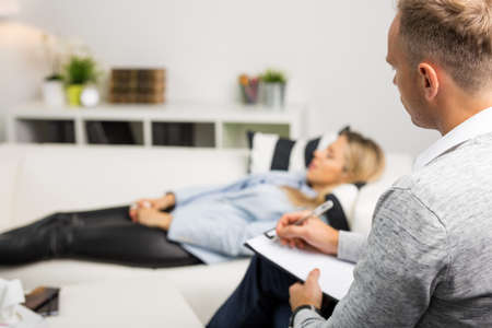 woman on couch: Woman lying on couch at doctors office
