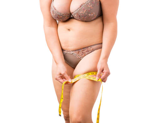 Overweight woman measuring her hip