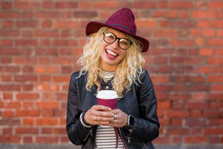 millennial: woman standing with coffee cup and smiling