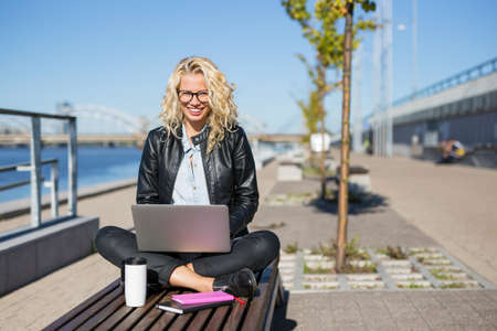 pier: Woman sitting outside with laptop in her lap
