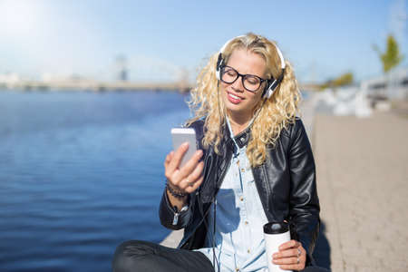 Woman using smartphone to listen to music Stock Photo