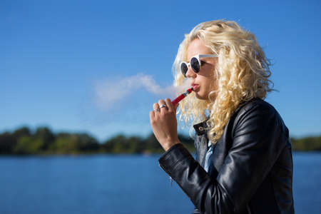Woman smoking electronic cigarette Stock Photo