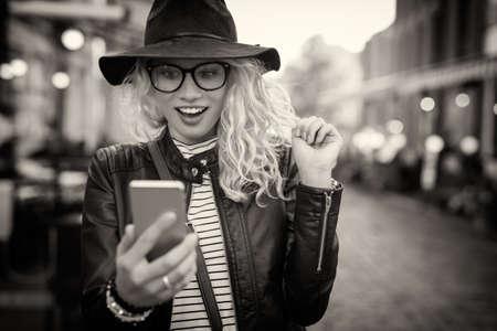 Imagen en blanco y negro de la mujer que mira su teléfono Foto de archivo - 66094213