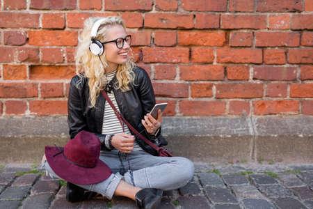 ipster レンガの壁のそばに座って、音楽を聴くこと