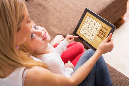 educational problem solving: Mother and child playing Sudoku together