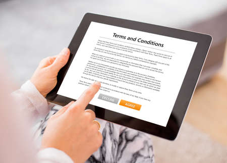 Person accepting terms and conditions on tablet Stockfoto