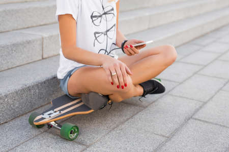 Woman using smartphone while sitting on longboard