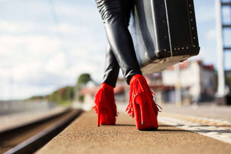 Female with red high heels and suitcase in train station