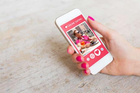Mujer que usa la aplicación de citas en línea en el teléfono móvil Foto de archivo - 66748840