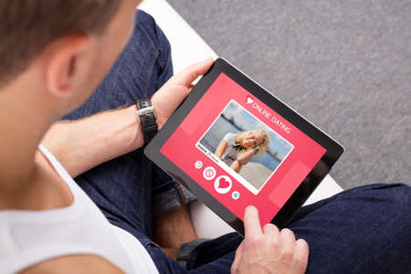 タブレットのオンライン出会い系アプリを使用している人 写真素材