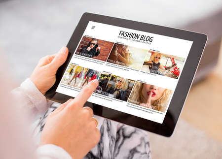 Woman reading fashion blog on tablet Banque d'images