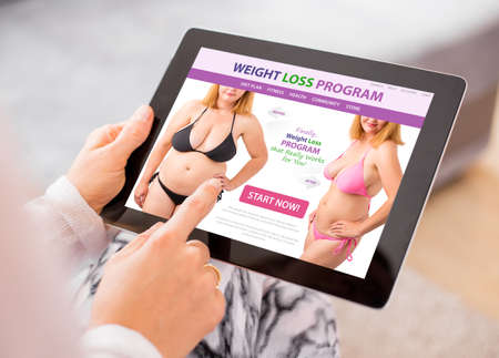 Woman reading about weight loss on tablet computer Stock fotó