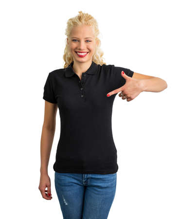 Woman in black polo T-shirt  pointing at it with one hand
