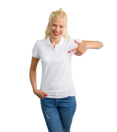 Woman in white polo T-shirt  pointing at it with one hand