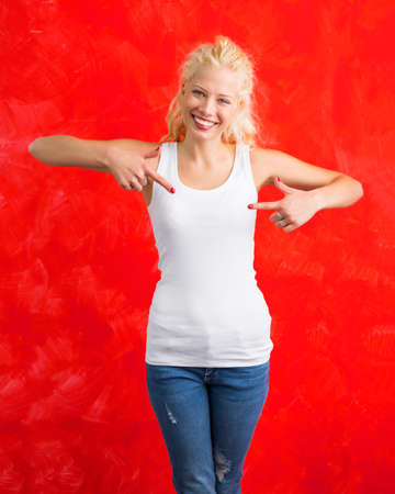 Woman in white tank-top shirt on red background  pointing at it with both hands