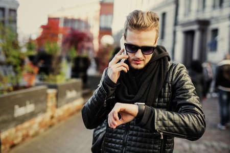 Mann in der Stadt im Gespräch über das Telefon und Blick auf Smartwatch