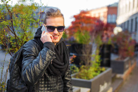 young male: Handsome man talking on the phone and smiling Stock Photo