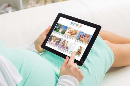 Pregnant woman reading baby blog on tablet
