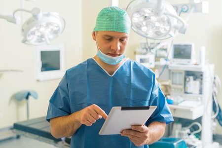 Docteur en utilisant un ordinateur tablette dans la salle de chirurgie