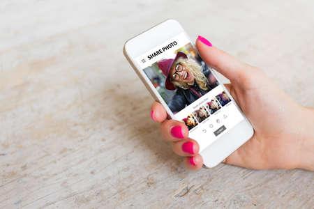 Vrouw met behulp van delen van foto's app op de telefoon Stockfoto